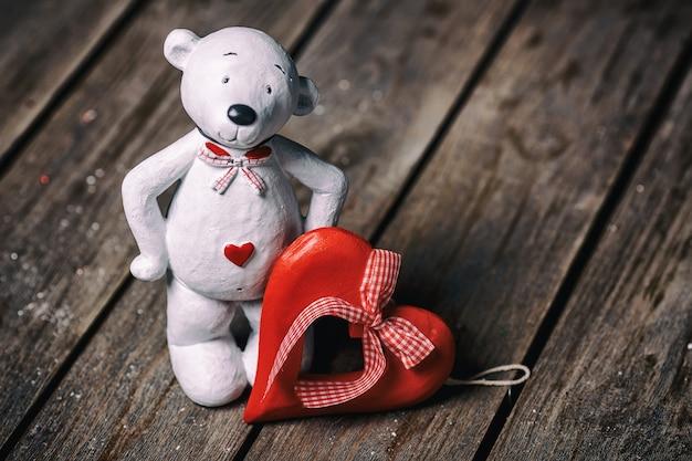 Boneca urso branco com coração de pé no fundo de madeira velho. conceito de dia dos namorados.