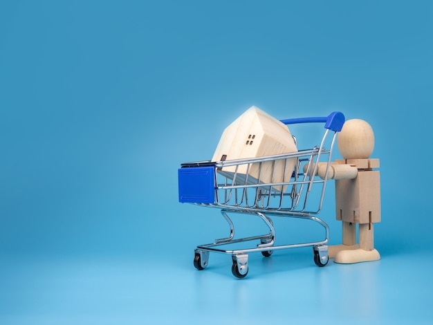 Bonecas de madeira que ficam ao lado do carrinho de compras com uma casa de madeira modelo em azul