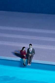 Bonecas sentadas ao lado da piscina
