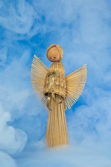 Boneco anjo vintage de palha de palha de madeira contra um fundo azul com fumaça nebulosa