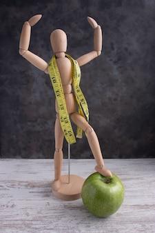 Boneco de madeira com as mãos para cima posando com fita centímetro e maçã verde