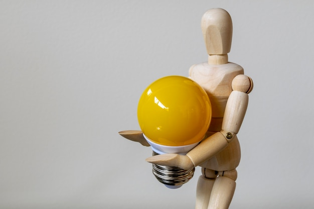 Boneco de madeira com lâmpada amarela. conceito de ideia