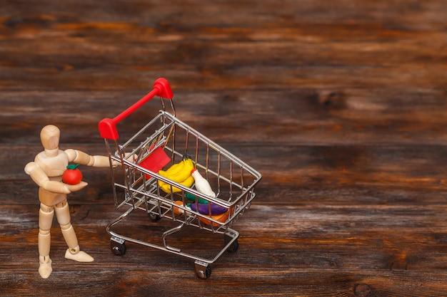 Boneco de madeira com mini carrinho de compras. conceito abstrato de comida