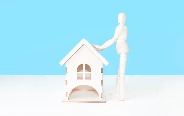 Boneco de madeira constrói uma casa de madeira