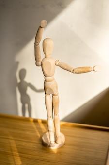 Boneco de madeira embaixo da mesa dançando pose vista de close