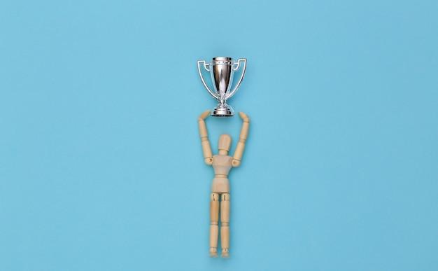 Boneco de madeira feliz segurando uma taça do campeonato de prata sobre um fundo azul