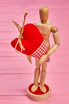 Boneco de madeira humano segurando o coração.