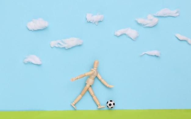 Boneco de madeira joga futebol com uma bola em um campo feito à mão no céu cheio de nuvens