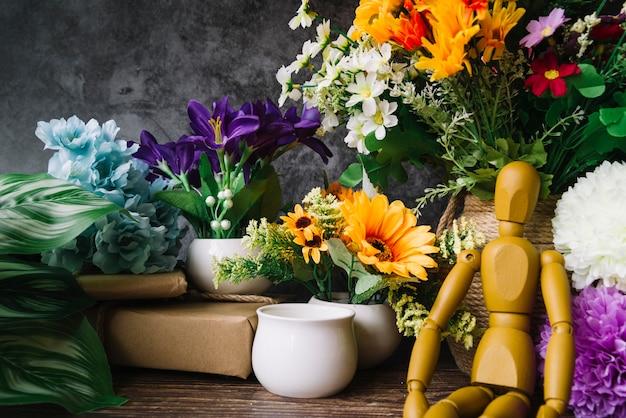 Boneco de madeira sentado em frente a flores coloridas na mesa