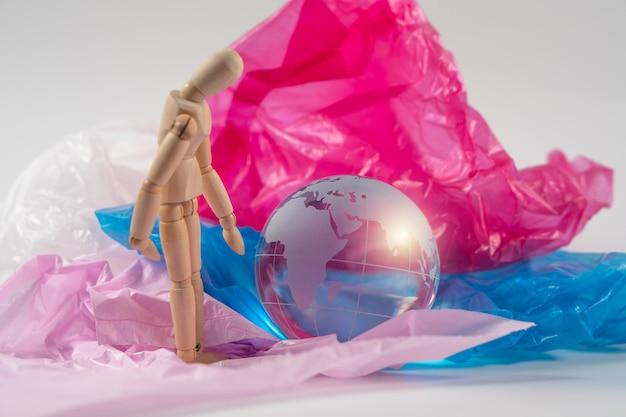 Boneco de madeira tocar o globo de cristal em saco plástico e se sentir preocupado e tem que proteger a terra.
