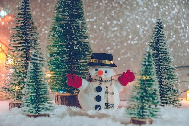 Boneco de neve com árvore de natal e enfeite. fundo de brilho.