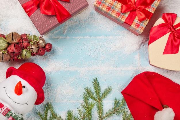 Boneco de neve com caixas de presente, galho de árvore do abeto, chapéu de papai noel na superfície de madeira azul nevado