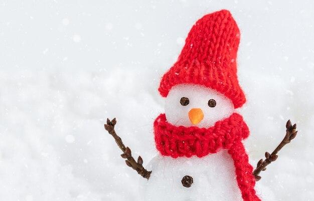 Boneco de neve com chapéu vermelho e lenço no fundo de neve