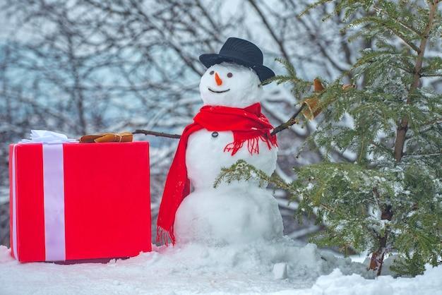 Boneco de neve com recentemente cortou a árvore de natal na floresta. jovem boneco de neve lenhador carrega pinheiro em