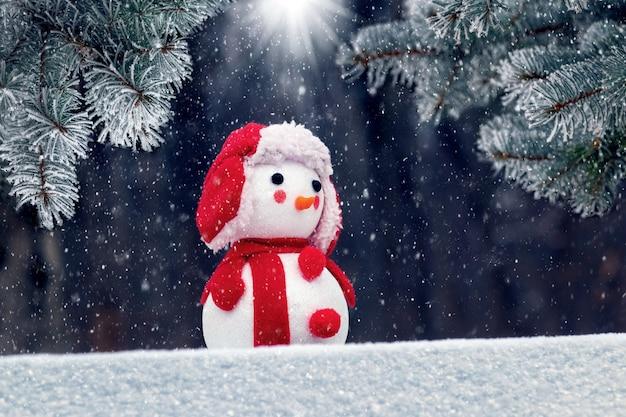 Boneco de neve com um chapéu vermelho na floresta perto das árvores de natal durante uma nevasca sob os raios de luz