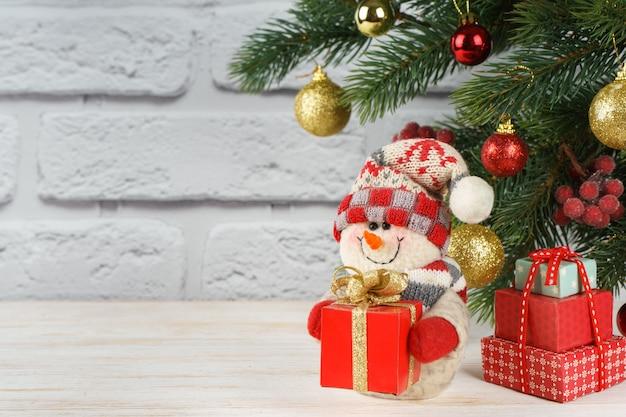 Boneco de neve de ano novo com caixa de presente vermelha no fundo da árvore de natal decorada