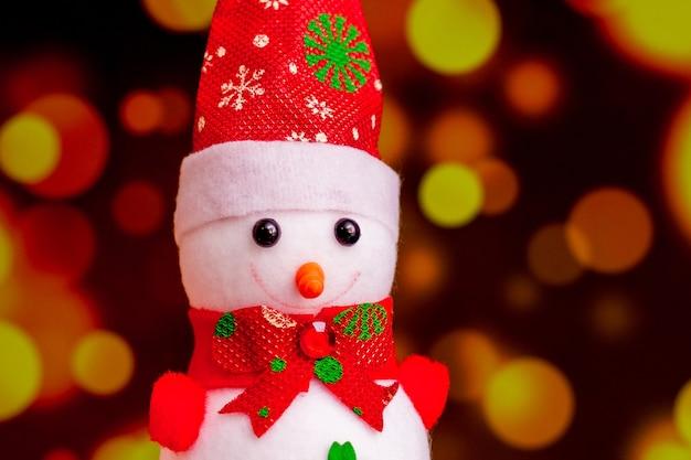 Boneco de neve de brinquedo em um fundo vermelho embaçado com bokeh. comemorando natal e ano novo_