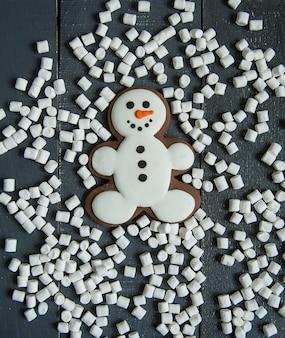 Boneco de neve de gengibre com marshmallow deitado no fundo cinza de madeira.