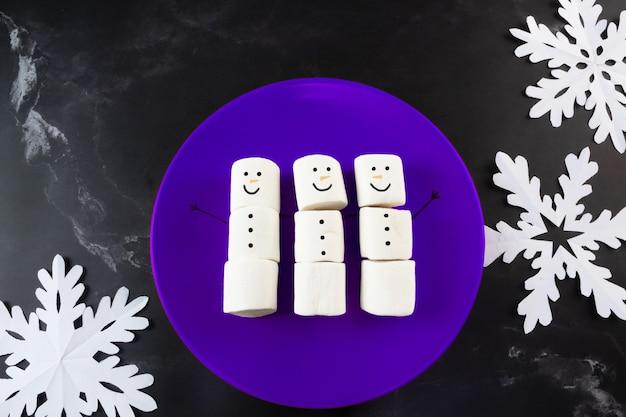 Boneco de neve de marshmallows na placa azul e flocos de neve ao lado
