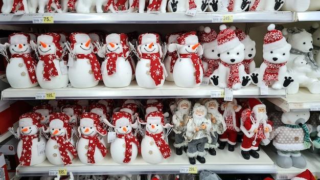 Boneco de neve do papai noel com decorações de natal vende no balcão da loja