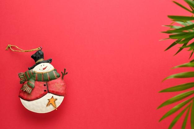 Boneco de neve e ornamento de folhas verdes em fundo vermelho