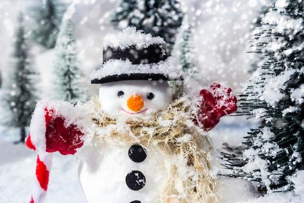 Boneco de neve em bosques de pinheiros durante o inverno para o natal