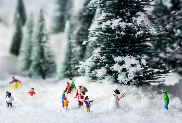 Boneco de neve em miniatura e as pessoas saem em bosques de pinheiros durante o inverno