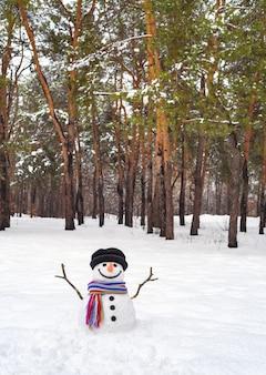 Boneco de neve engraçado em uma floresta de pinheiros. diversão de inverno com neve