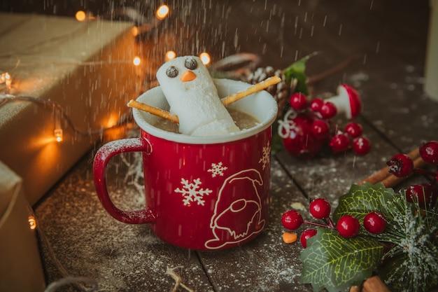 Boneco de neve na caneca de café sob chuva de pó branco