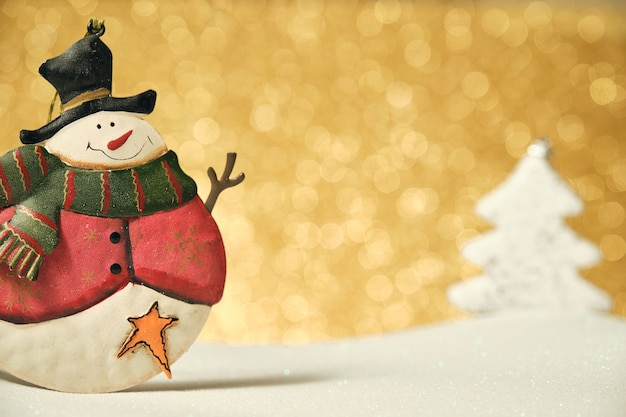 Boneco de neve na superfície branca e fundo dourado brilhante