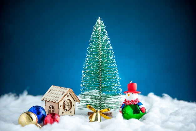 Boneco de neve pequeno, árvore de natal, árvore de natal, brinquedos de bola na superfície azul