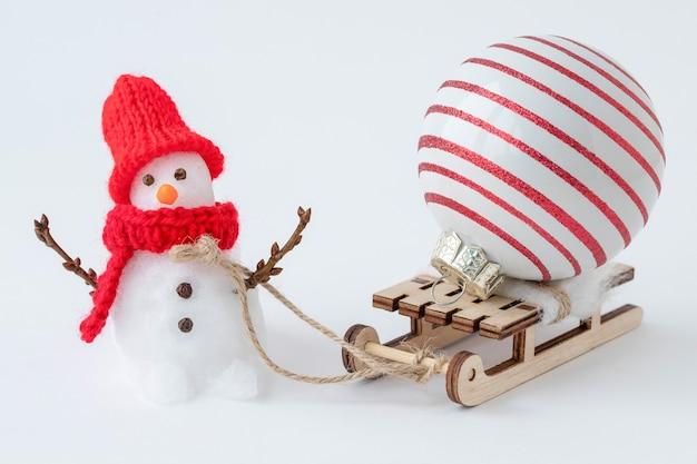 Boneco de neve pequeno com trenó e enfeite de natal