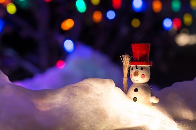 Boneco de neve vintage na neve em fundo de noite com luzes de natal