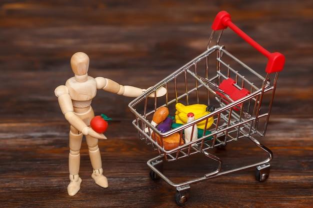 Boneco fictício de madeira com mini carrinho de compras