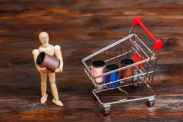 Boneco fictício de madeira e mini carrinho de compras com carretéis de linha