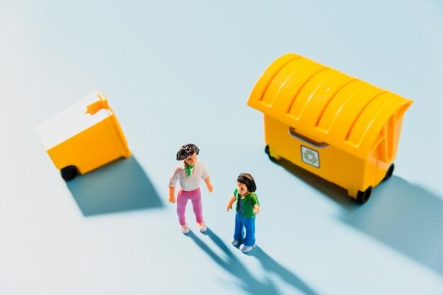 Bonecos ao lado de um recipiente de reciclagem amarelo