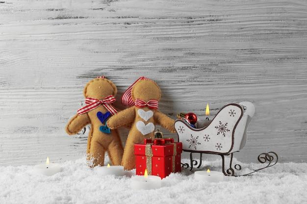 Bonecos de feltro com trenós do papai noel, velas e brinquedos em uma mesa de madeira com neve, natureza morta