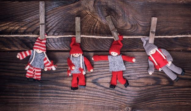 Bonecos de madeira em roupas de inverno pendurar em uma corda