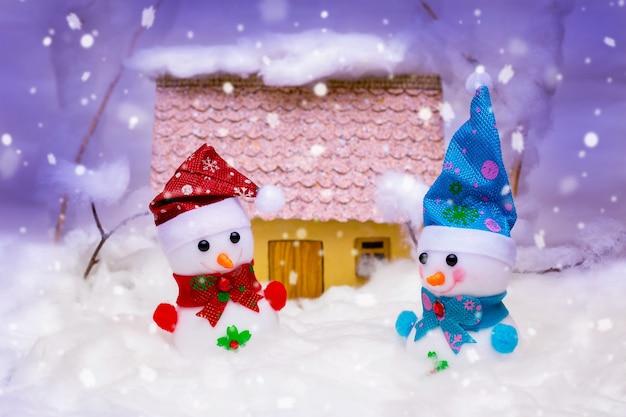 Bonecos de neve de brinquedo com a casa durante a queda de neve