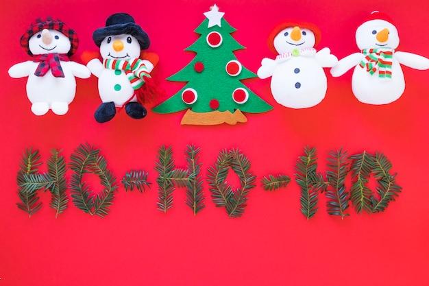Bonecos de neve de brinquedo e árvore de natal perto de inscrição