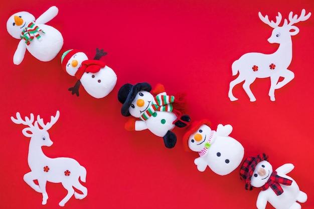 Bonecos de neve de brinquedo pequeno com veados na mesa