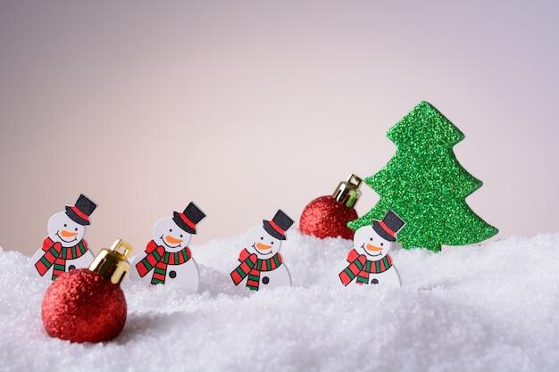 Bonecos de neve de enfeite de natal, árvore de natal e bolas vermelhas na neve