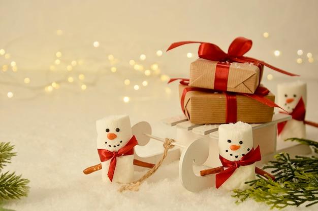 Bonecos de neve de marshmallow com trenó, caixas de presente