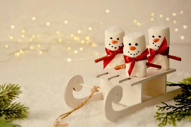 Bonecos de neve de marshmallow com trenó, maquete abstrata de natal com bokeh e ramos de abeto