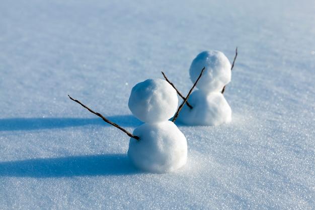 Bonecos de neve feitos de neve no inverno, pequenos bonecos de neve ficam na neve no inverno