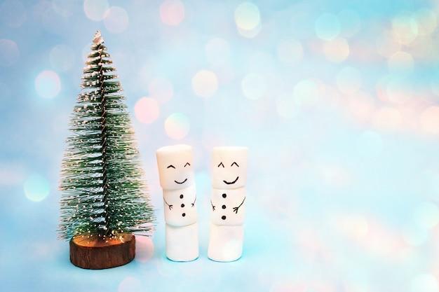 Bonecos de neve ficam perto de uma pequena árvore de natal na neve, foto com efeito bokeh.