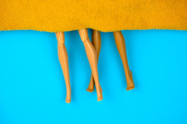 Bonecos de plástico vista superior sob manta laranja sobre fundo azul, conceito de sexo