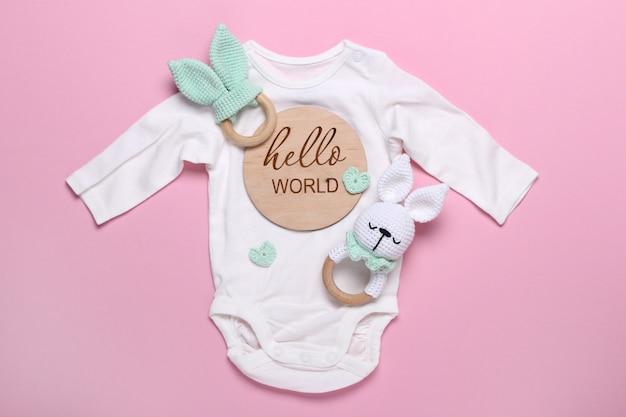 Bonequinho de bebê branco para brinquedos de madeira, beanbag e mordedores tablet de madeira no fundo rosa