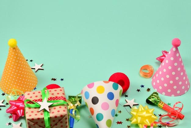 Bonés de aniversário, presentes, confetes, fitas, estrelas, narizes de palhaço em uma superfície verde