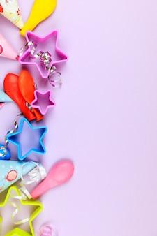 Bonés de festa de aniversário, balão e estrelas no fundo roxo